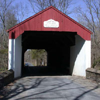 This bridge spans Cabin Run Creek, named for the many small houses along its banks in the 1800s.  It is on Covered Bridge Road in Plumstead Township, downstream from Loux Covered Bridge and near the historic Stover-Myers Mill.<br>